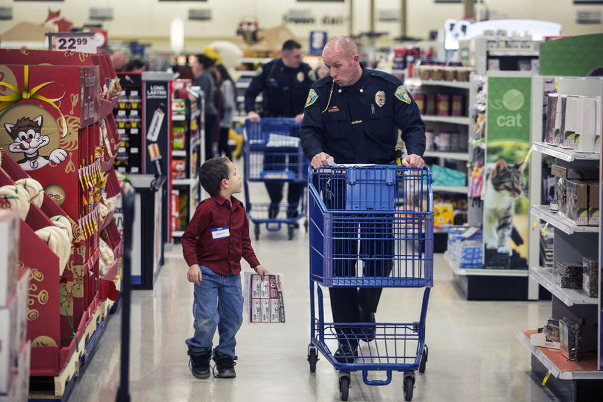Rodney Roten, deputy chief of the Midland Police Department, right, and Steven Eddy, 6, of Midland, deliberate on where to begin a $100 shopping spree during the Shop with a Hero event on Wednesday at Meijer.
