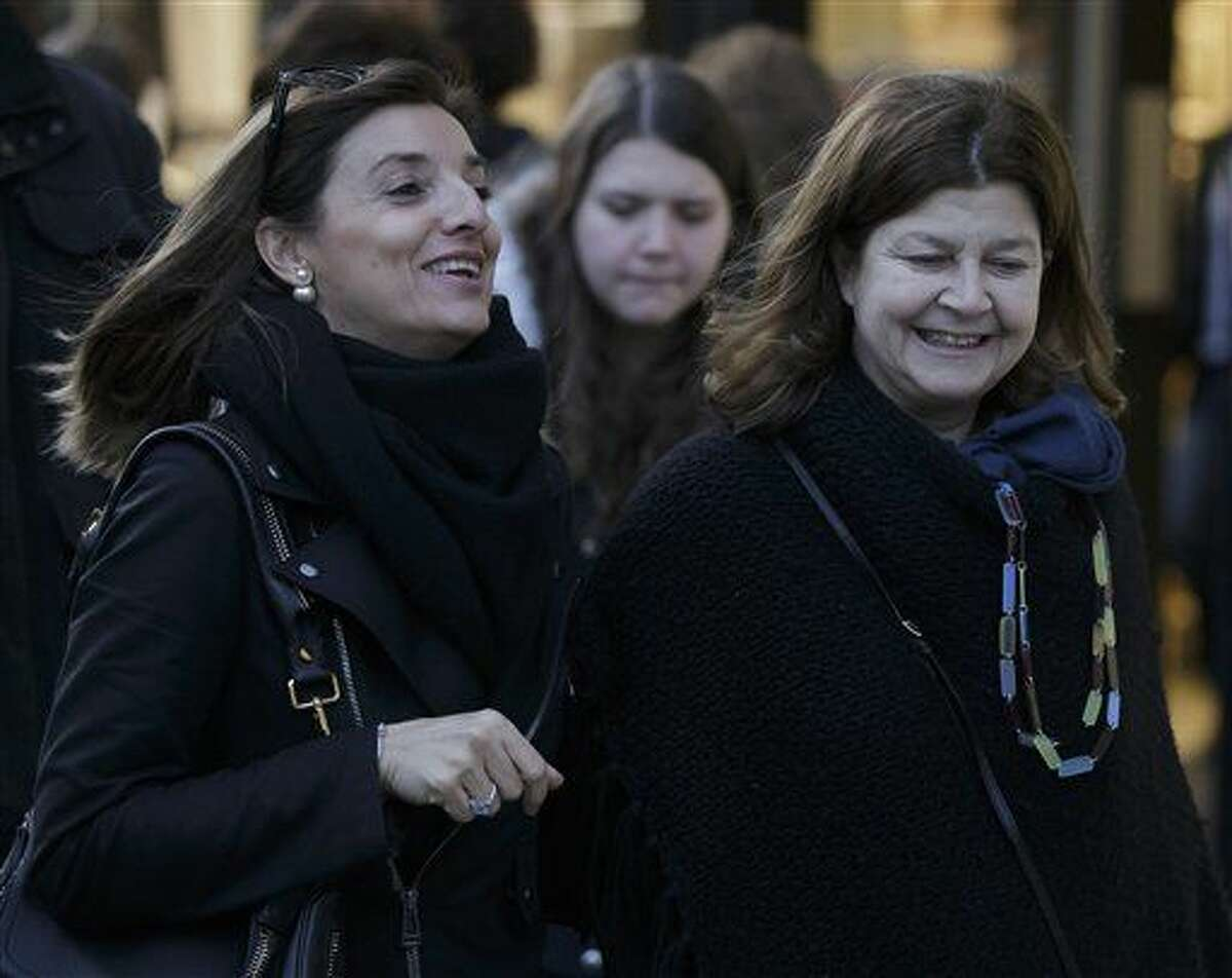 Women smile as they walk down Oxford Street, in London, Wednesday, Dec. 9, 2015. There's good news for grumpy women: Being happy apparently has no effect on how long you might live. That's the conclusion of the latest attempt to find out if happy people live longer. Previous studies have linked happiness to longevity but researchers now say there's no such scientific connection. (AP Photo/Tim Ireland)