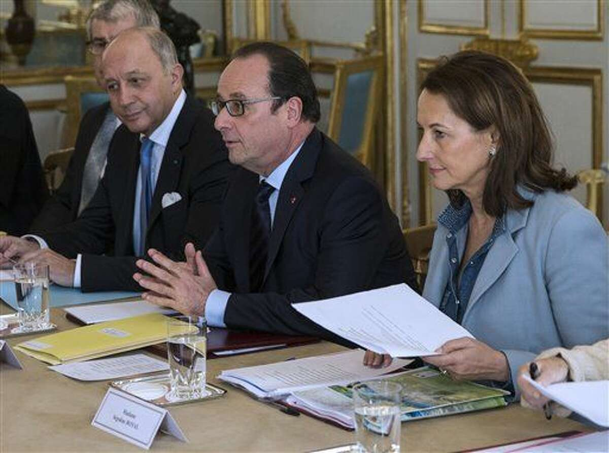 French President Francois Hollande, center, his Foreign Affairs Minister Laurent Fabius, left, and Ecology Minister Segolene Royal meet with representatives of NGOs specialized in environmental issue at the Elysee Palace in Paris, Saturday, Nov. 28, 2015. French President Francois Hollande was meeting with environmental groups Saturday, pushing for an ambitious global deal to reduce man-made emissions blamed for global warming.