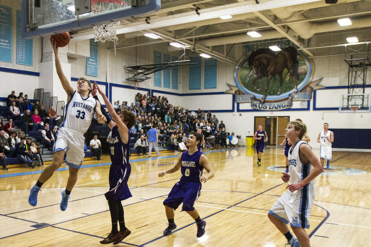 Meridian's Nick Lueder scores on a layup while being defended by Farwell's Scott Lucia in a game at Meridian High School Friday night.