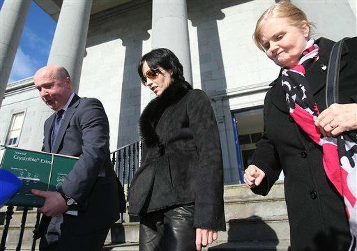 La cantante Dolores O'Riordan, centro, sale de la corte del distrito de Ennis acompañada por su madre Eileen y el abogado Bill O'Donnell, en Ennis, Irlanda, el miércoles 24 de febrero de 2016. La vocalista de la banda de rock irlandesa The Cranberries fue multada por 6.000 libras esterlinas (6,600 dólares) por un incidente violento ocurrido en vuelo de Nueva York a Irlanda en noviembre de 2014. (Niall Carson/PA via AP) UNITED KINGDOM OUT NO SALES NO ARCHIVE