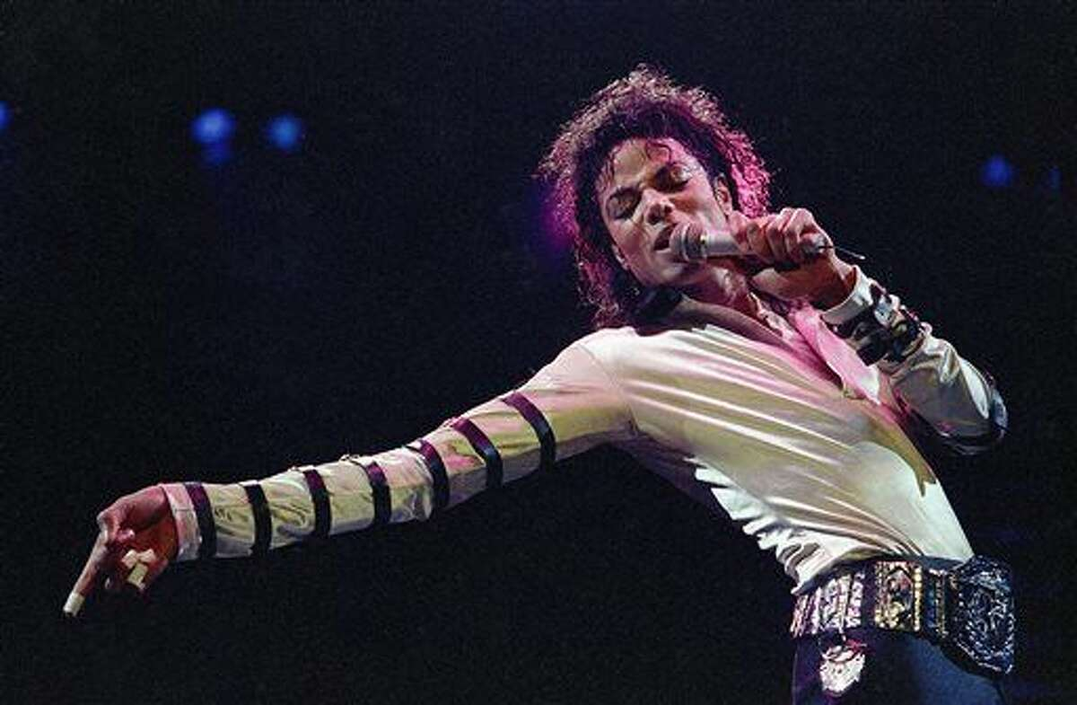 """FILE - In this Feb. 24, 1988 file photo, Michael Jackson leans, points and sings, dances and struts during the opening performance of his 13-city U.S. tour, in Kansas City, Mo. Jackson's """"Thriller"""" has broken another sales record, with the Recording Industry Association of America announcing Wednesday, Dec. 16, 2015, that the singer is the first artist to attain 30-time multi-platinum status after his album sold 30 million copies in the U.S. since its release in 1982. (AP Photo/Cliff Schiappa, File)"""