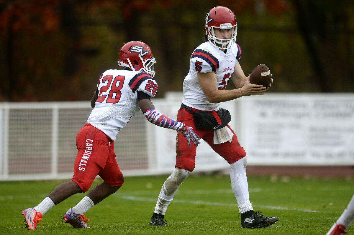Saginaw Valley State University quarterback Brad Odeman Jr., right, prepares to hand the ball off to Malik Washington during a recent game.