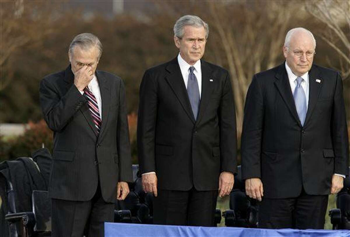 FILE - In this Friday, Dec. 15, 2006, file photo, Secretary of Defense Donald Rumsfeld, left, pauses as President George W. Bush, and Vice President Dick Cheney participate in Rumsfeld's farewell ceremony at the Pentagon in Washington. Former President George H.W. Bush is publicly criticizing for the first time key members of his son's administration. A biography of the nation's 41st president to be published in November, 2015, contains his sharply critical assessments of Cheney and Rumsfeld.