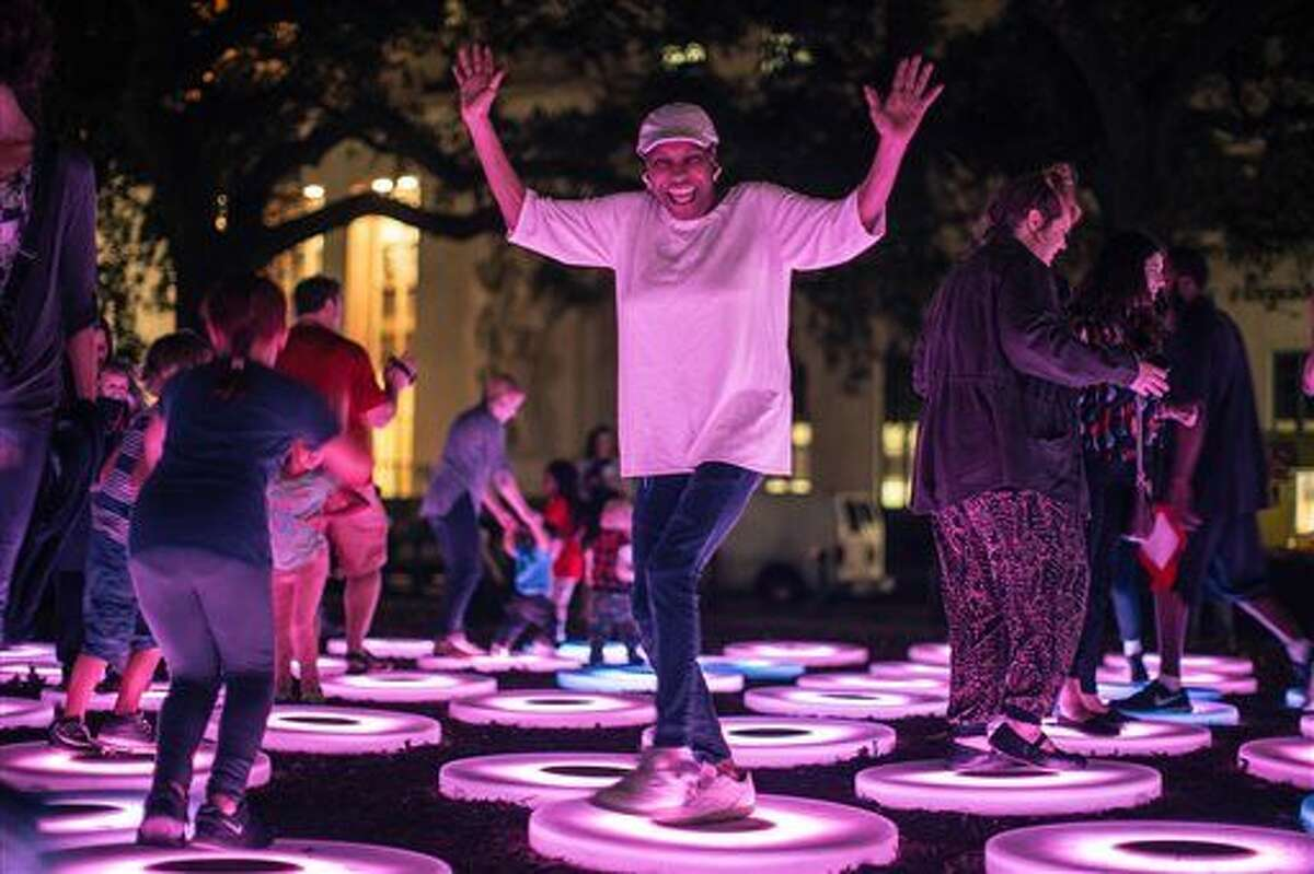 """CORRECTS NAME FROM JAN TO JEN - This Dec. 3, 2015 photo provided by Arts Council New Orleans shows people interacting with """"The Pool,"""" a work that was part of New Orleans' LUNA Fete light festival. The work, by artist Jen Lewin, is also going to be on display at Light City Baltimore, a light festival taking place in Baltimore March 28-April 3. Light festivals that combine contemporary art and technology, often with interactive features, are taking off as a trend. (Marcus Carter/Arts Council New Orleans via AP)"""