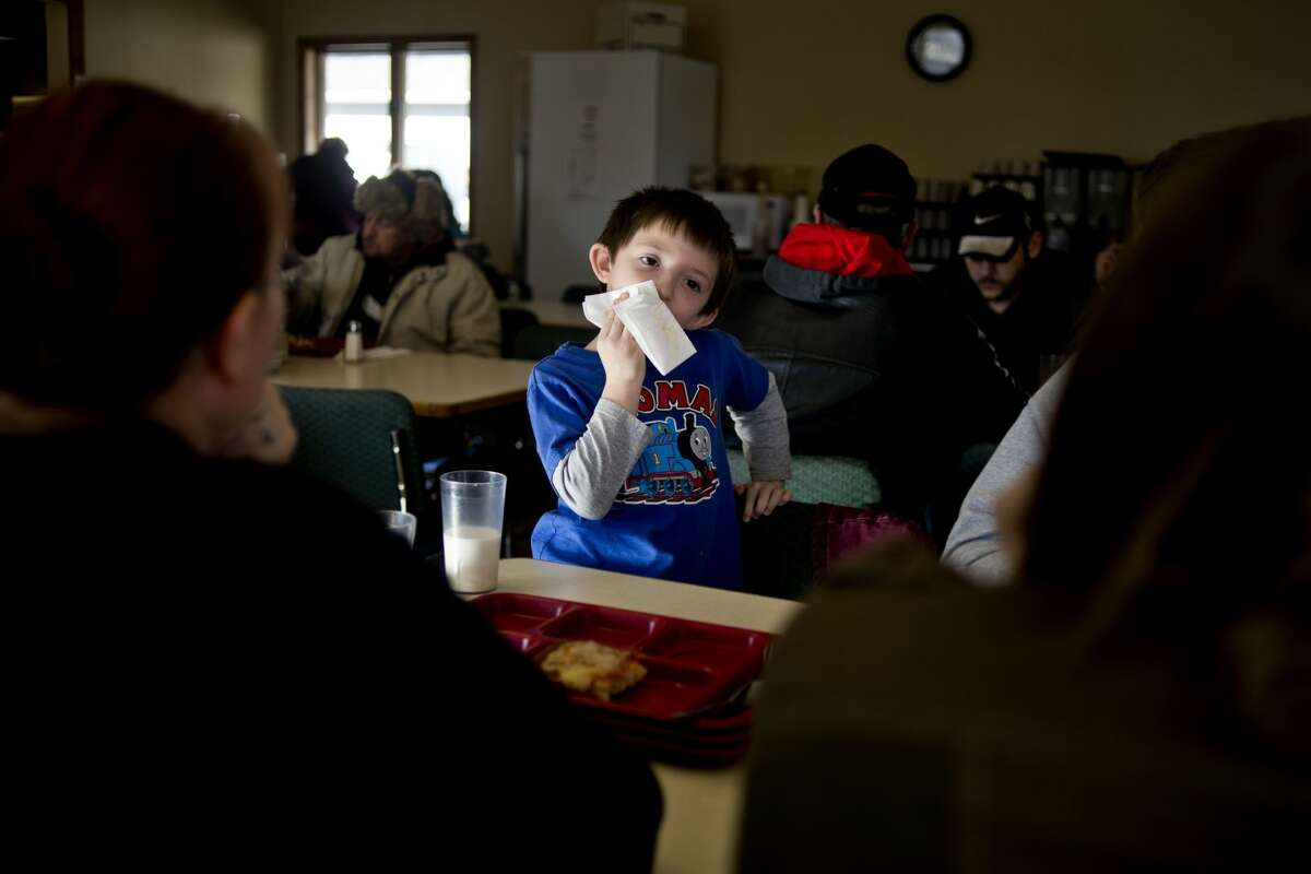 Royal Hulshizer, 7, of Midland, wipes his mouth after eating at Midland's Open Door soup kitchen on Wednesday. The Christ-centered facility is able to offer a far more varied and balanced menu, thanks in large part to Hidden Harvests' stepped-up efforts in Midland County.