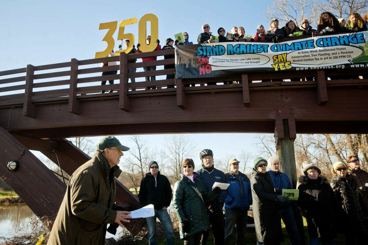 Lone Tree Council's Terry Miller, left, leads a group in a pro-environment pledge during the Global Climate Rally on Sunday at the Tridge. Participants assembled at the Tridge holding large 350 numbers, referring to 350 parts per million as the upper safety limit for atmospheric CO2. The group posed for pictures that could be shared via social media and chanted pro-environment phrases led by Miller and Saginaw Valley Sustainability Society's Pat Race.