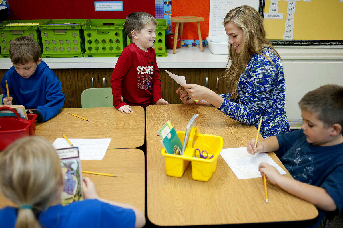 Northwood University senior Jordyn Nurenberg, right, looks over first-grader Jack McMenemy's sentences during Northwood University's Go Make A Difference (Go M.A.D.) Day at Woodcrest Elementary on Friday. Members of the women's basketball team helped students with spelling, writing and reading during Northwood's first Go M.A.D. day.