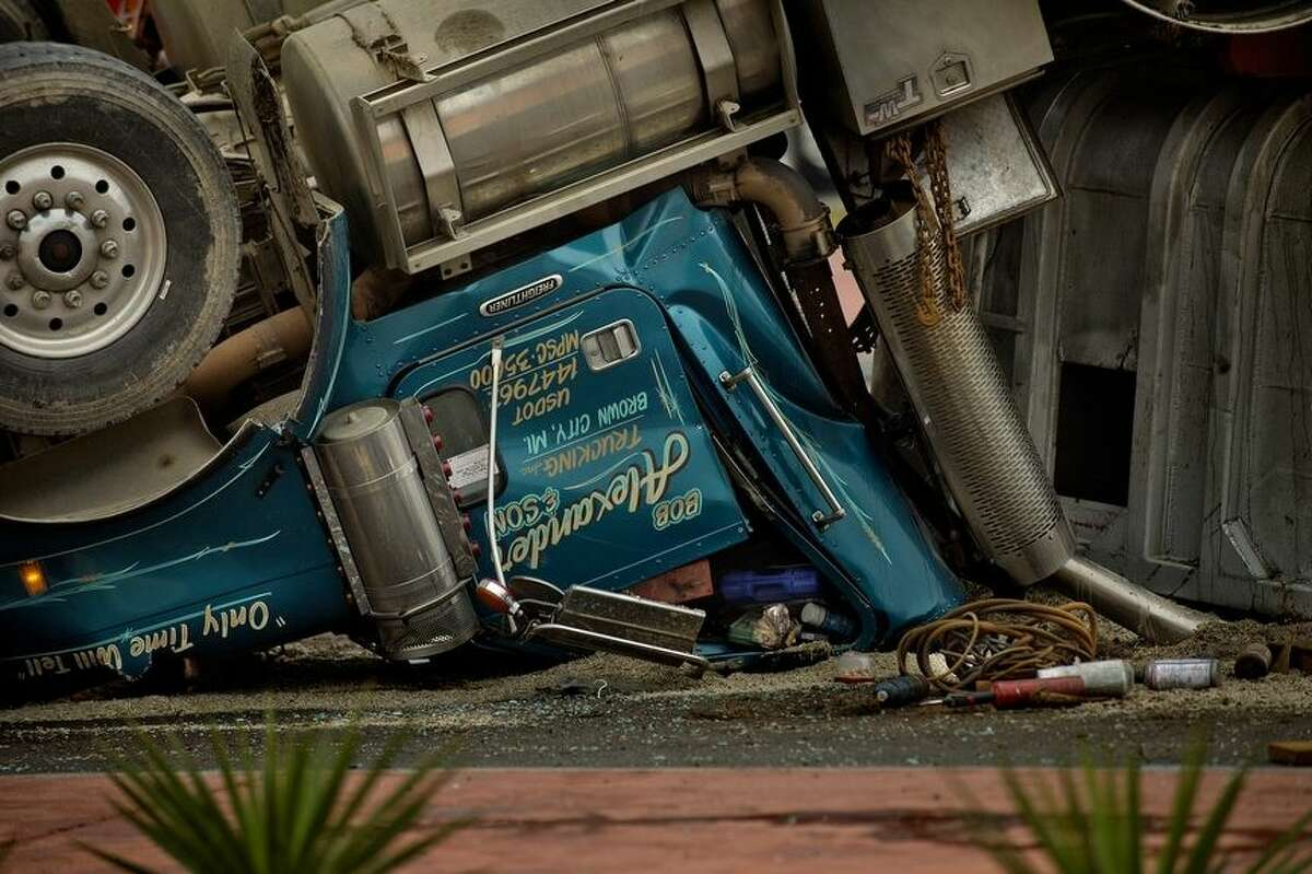 The crushed cab of a tandem semi truck trailer that crashed and overturned on the westbound Business 10 roundabout on Monday morning in Midland. Rescue personnel extracted the driver who was pinned inside the cab. The driver was taken to MidMichigan Medical Center-Midland for treatment.