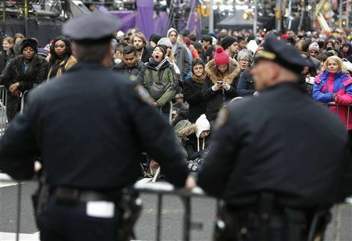 Police officers look over a crowd waiting for midnight in Times Square in New York, Thursday, Dec. 31, 2015. Around 1 million people are expected to converge on Times Square for the annual New Year's Eve celebration. This year's festivities will also be attended by nearly 6,000 New York City police officers, including members of a specialized counterterrorism unit. (AP Photo/Seth Wenig)