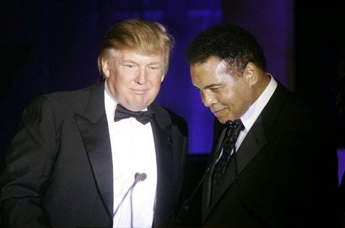 """FILE - In this March 24, 2007, file photo, Donald Trump, left, accepts his Muhammad Ali award from Ali at Muhammad Ali's Celebrity Fight Night XIII in Phoenix, Ariz. Ali is criticizing Republican presidential front-runner Trump's proposal to ban Muslims from entering the United States, and calling on Muslims """"to stand up to those who use Islam to advance their own personal agenda."""" (AP Photo/Jeff Chiu, File)"""