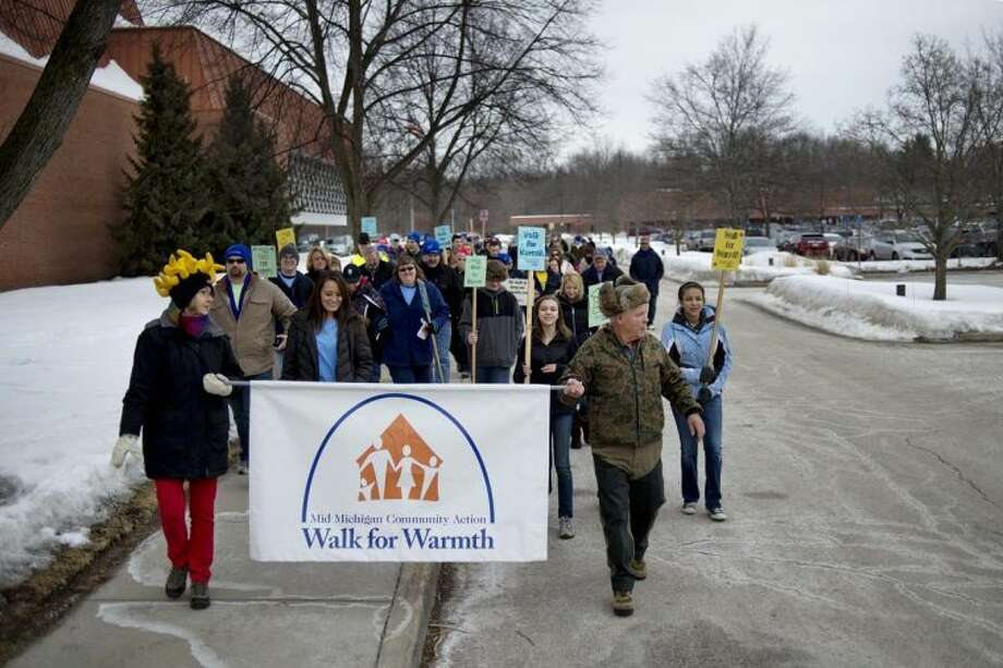 Kiwassee Kiwanis Club members Diane Stevens, left, and Millard Kent, right, hold a sign and lead the crowd at the start of the Mid Michigan Community Action Agency's Walk for Warmth in this 2014 file photo. This year marks the 25th anniversary of the Walk for Warmth. Photo: Nick King |  Daily News File Photo
