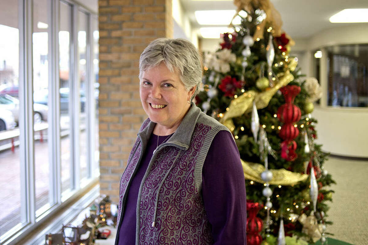 Anita Barrett decorates two large sections in the windows at the downtown Midland Chemical Bank. The two sections feature a rural scene on one side and residential on the other.