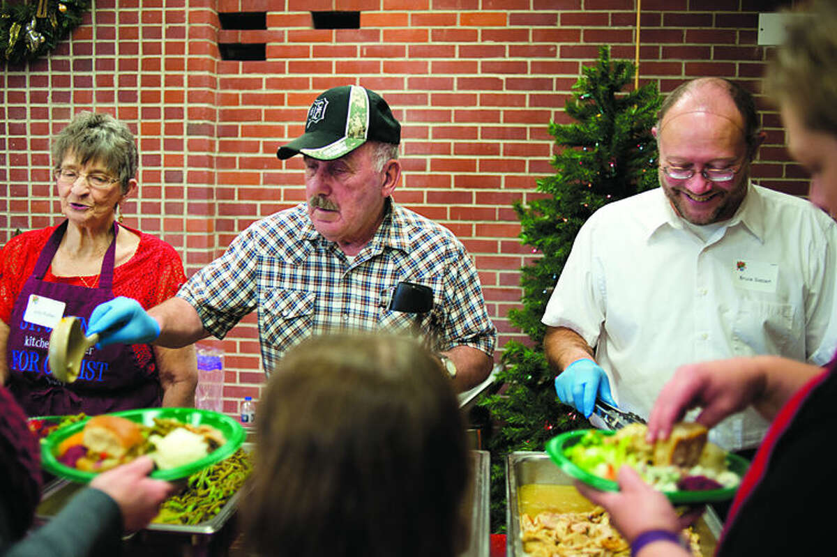 """St. John's Lutheran Church members from left: Judy Ruttan, Elmer Thurston and Bruce Siebert dishes out servings of gravy, green beans and turkey during the church's Christmas dinner Friday. This is St. John's 11th year hosting the free dinner to members of the community. More than 150 volunteers delivered and served meals on Christmas day. Nineteen turkeys, 80 pounds of ham and 150 pounds of potatoes were donated from local businesses, churches and non-profits for the meal. """"This dinner is meant for people to come together have a hot meal and fellowship,"""" Joyce Battjes, St. John's Christmas dinner committee coordinator said. """""""