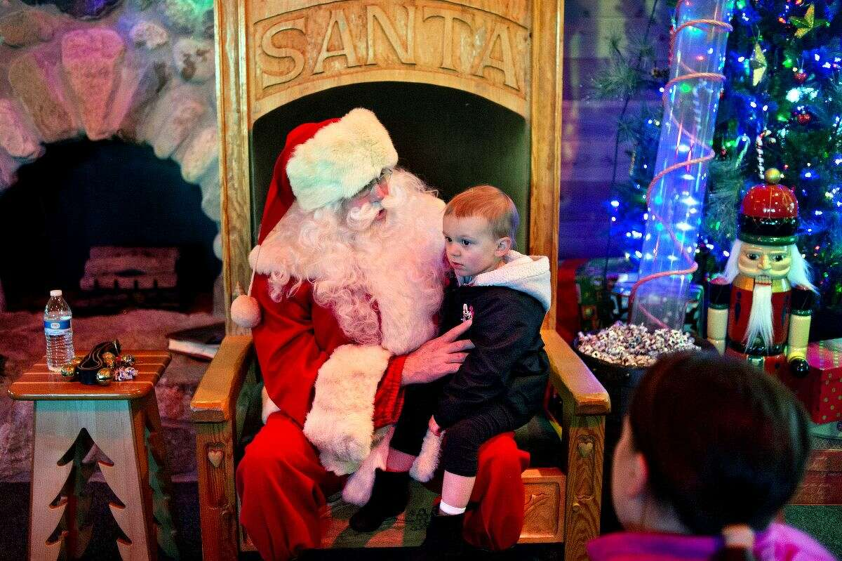 NICK KING | nking@mdn.net Santa Claus visits with Lillian Sanderman, 2, while Lillian's parents Kyle and Megan wait off the the side on Saturday at the Santa House in Midland. The Santa House is open every day in December leading up to Christmas Eve.
