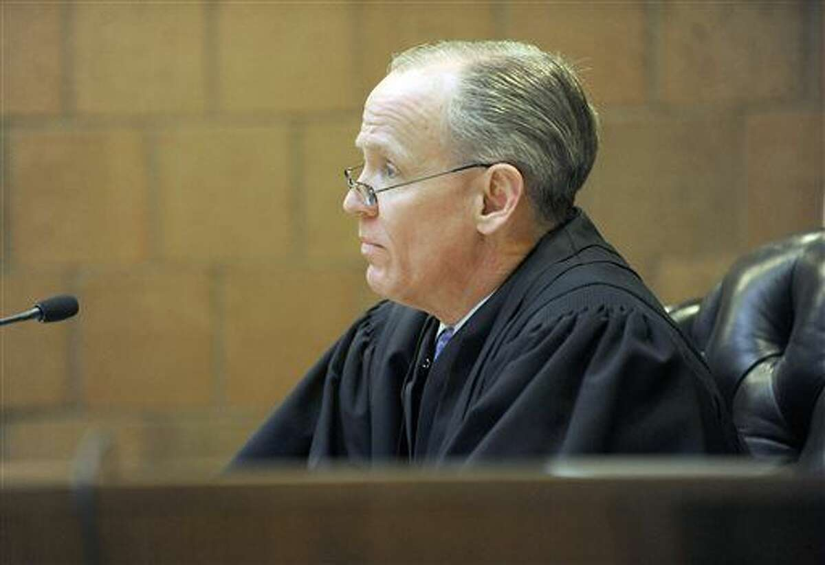 """FILE - In a Feb. 12, 2014 file photo, 55th District Court Judge Tom Boyd questions a defendant in Mason, Mich. Without a comma of dissent, the Michigan Supreme Court struck down an enduring practice that had brought millions of dollars to local courts from people convicted of crimes. Lawmakers from both parties swiftly trumped the ruling by passing a law that legalized the custom. """"This was a bad idea,"""" said Thomas Boyd, a judge in Ingham County who will be the next president of a statewide group of District Court judges. (Greg DeRuiter/Lansing State Journal via AP, File)"""