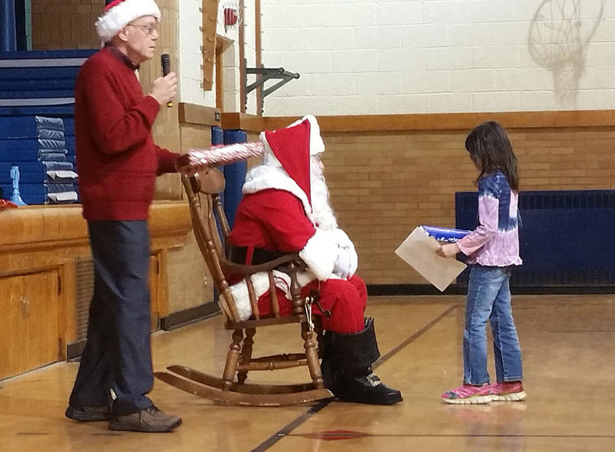 Kiwassee Kiwanis member Duane Townley stands next to Santa as a child was being greeted and presented a gift.