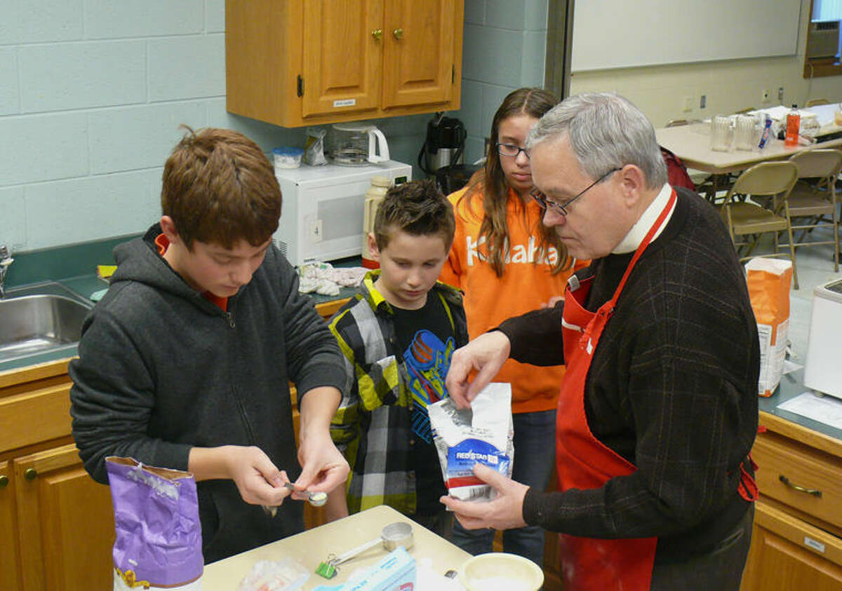 Students Zach Klement, Luke Mason and Abry Waters watch as Pastor John Seifert shows them how to use a bread machine.