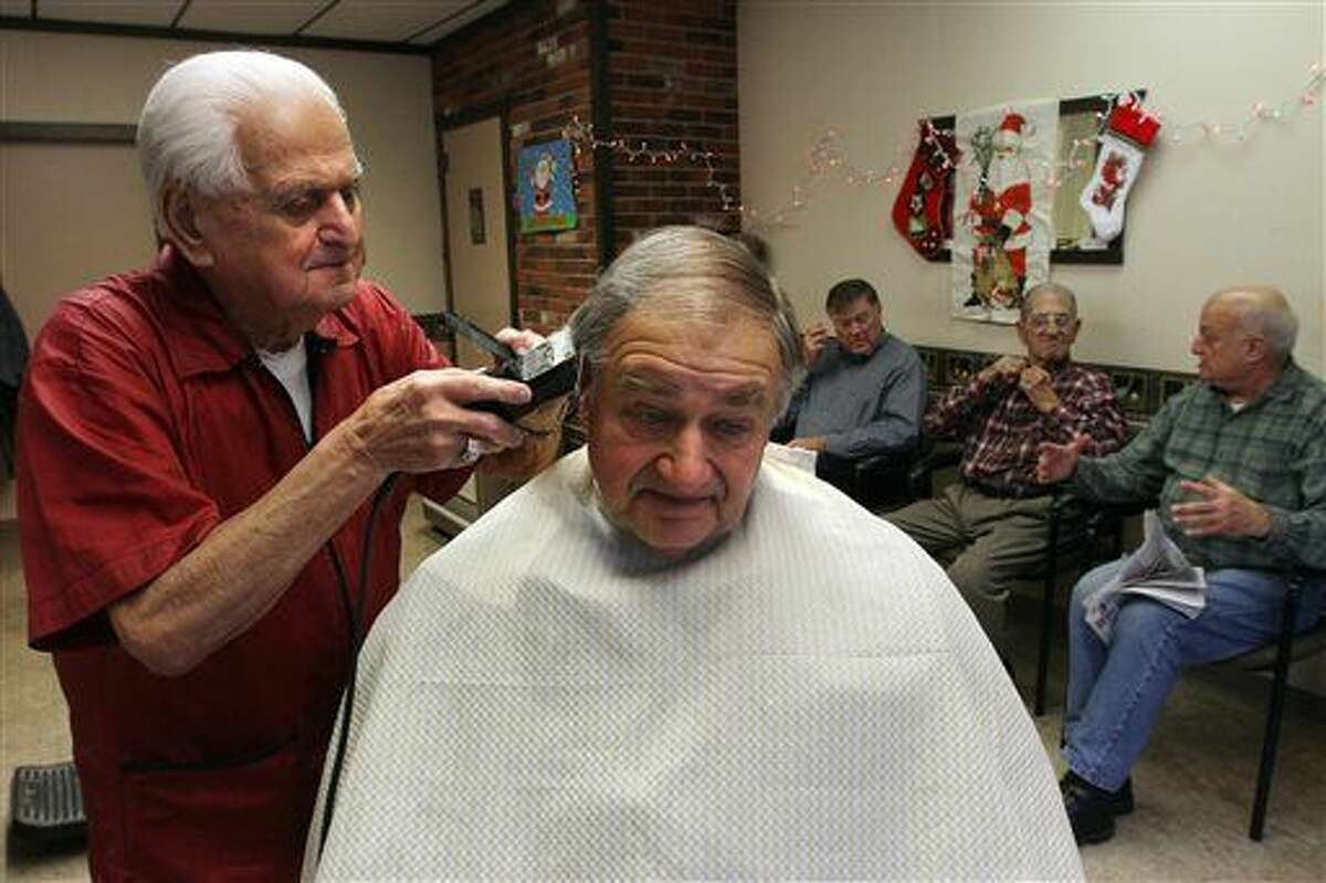 In this Dec. 21, 2015, photo, Tony Manzi cuts hair at Manzi's Barber Shop in Cranston, R.I. The 90-year-old Rhode Island barber is putting down his clippers after 68 years. Manzi has cut five generations of hair at the shop. (Bob Breidenbach/Providence Journal via AP)