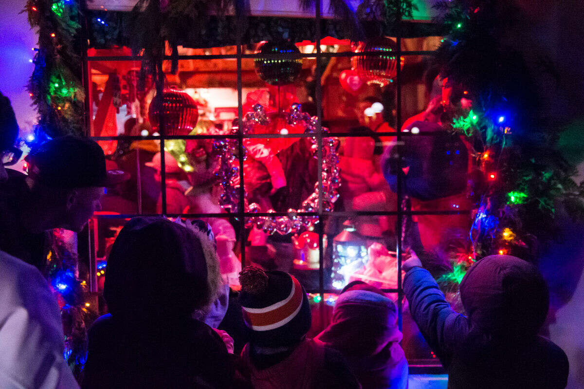 In this Daily News file photo from last year's Courthouse Lighting Ceremony, children peek through a window at the Santa House while waiting in line for a chance to sit with Santa Claus and hand deliver their Christmas wish list to him.