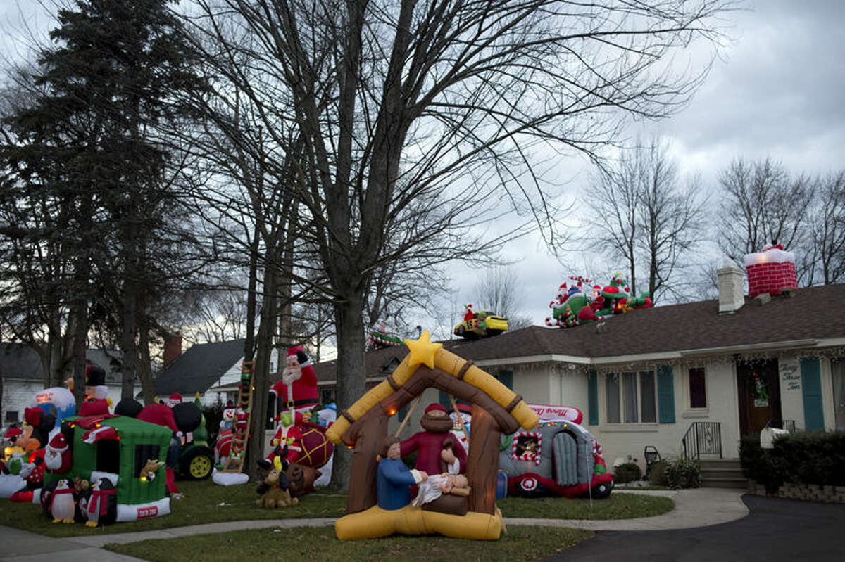 """Tom McCann of Midland decorated his front yard with 38 different types of inflatable holiday decorations for the season. """"The wife used to tell me it's tacky,"""" McCann said. """"But she thinks differently now."""""""