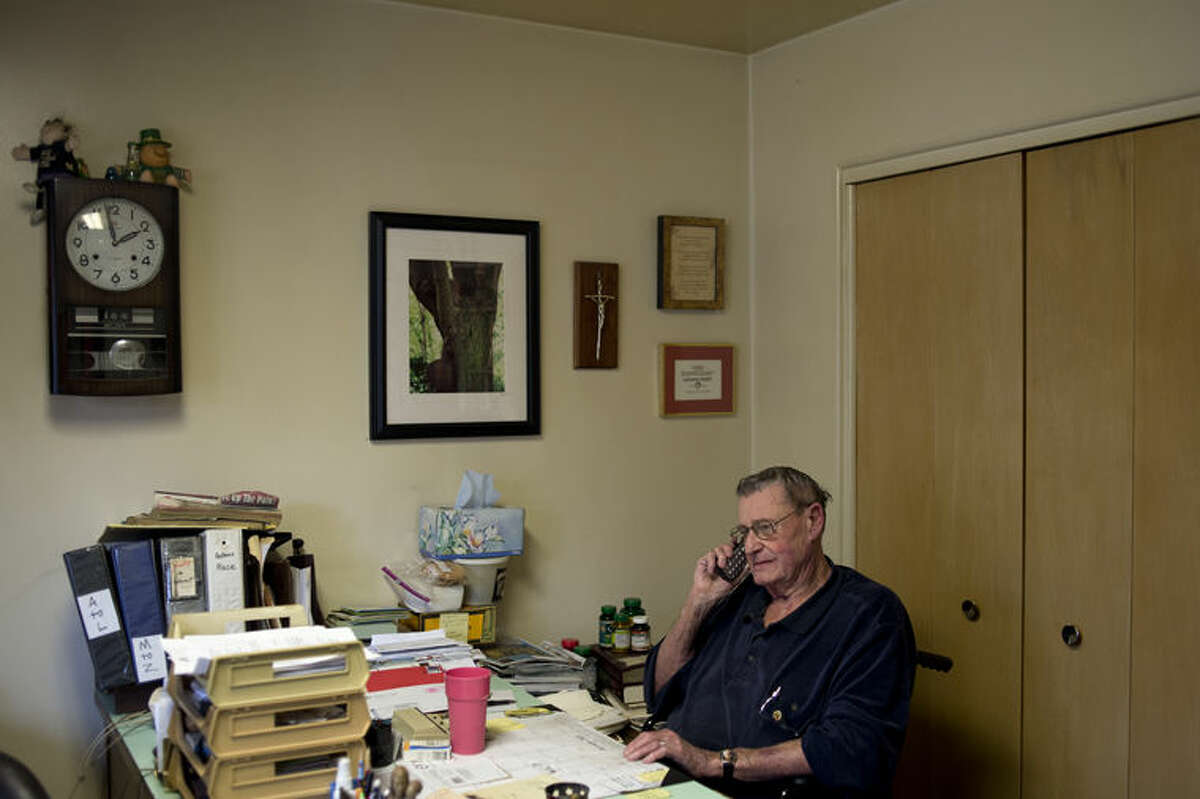 """Tom McCann of Midland talks on the phone inside his home office on a Friday afternoon. For the past 15 years McCann has decorated his front yard with holiday inflatables, this year he has 38 different types in his front yard and on the roof of his house. """"I can't go to the hospital to entertain the kids,"""" McCann said. """"But this way I can."""""""