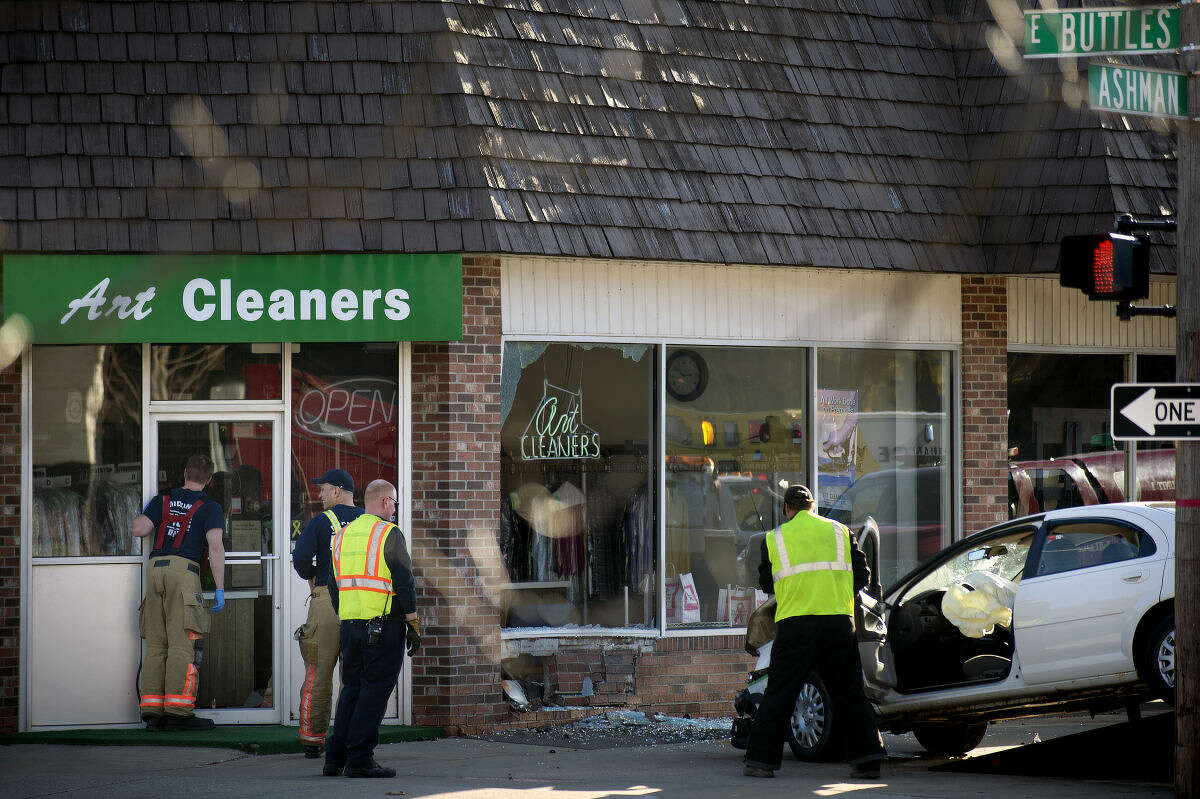 Midland firefighters work at the scene of a two-car crash at the corner of Buttles and Ashman streets on Sunday afternoon in Midland.