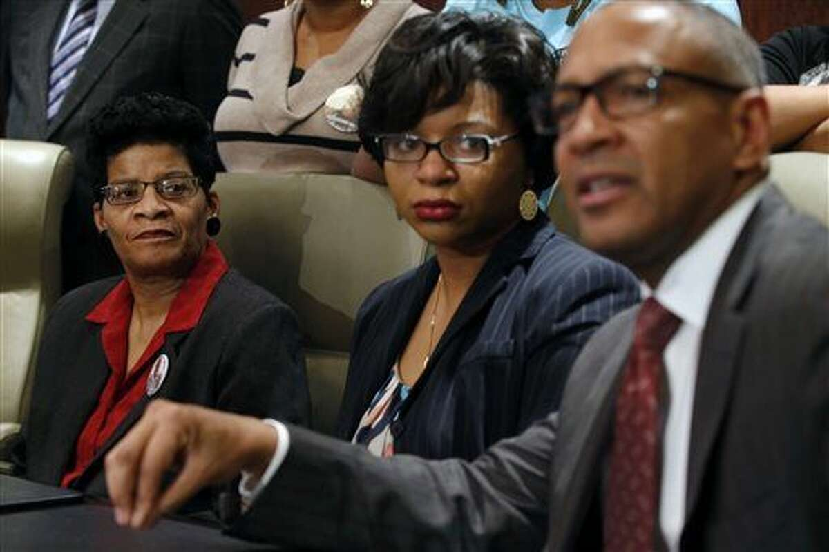 Geneva Reed-Veal, left, and Sharon Cooper, center, the mother and sister of Sandra Bland, listen to attorney Larry Rogers Jr., right, explain concerns about the Texas grand jury's role in the death of Naperville resident Sandra Bland Monday.The grand jury decided that no felony crime was committed by the sheriff's office or jailers in the treatment Bland, who died in a Southeast Texas county jail last summer.