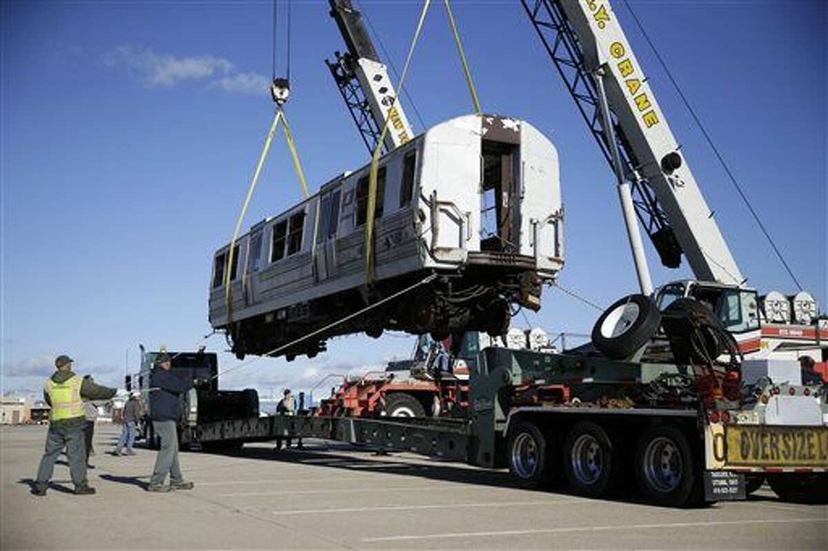 A damaged carriage of a PATH train that once carried commuters from New Jersey to the World Trade Center is loaded on to a truck in a cargo area of John F. Kennedy International Airport in New York, Tuesday, Dec. 15, 2015. This car is headed to the Trolley Museum of New York in Kingston, where it will be the centerpiece of a future Sept. 11 wing. (AP Photo/Seth Wenig)