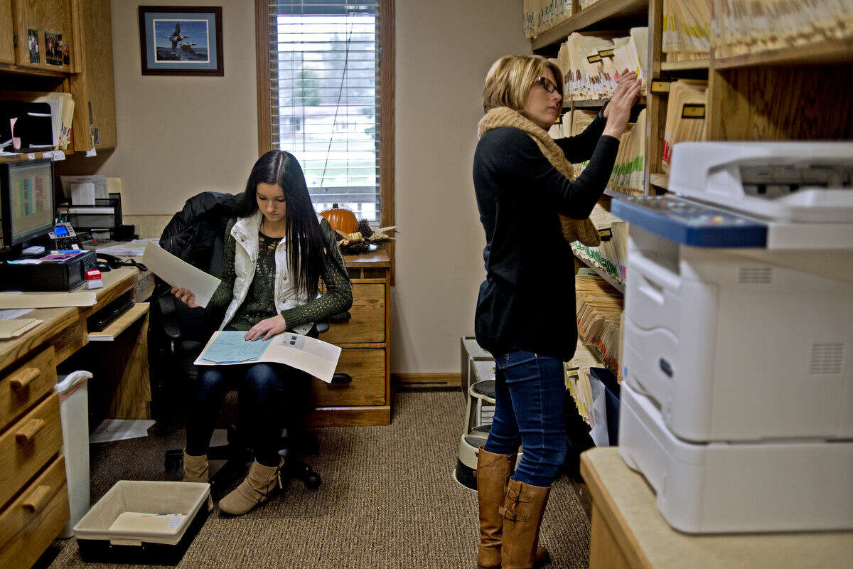 Meridian Early College student Tessa Weisenberger, 17, files paperwork at her co-op job as an office assistant at Michael Bowen Dentistry as office assistant Stephanie Nadenoff, right, looks through folders on Friday.