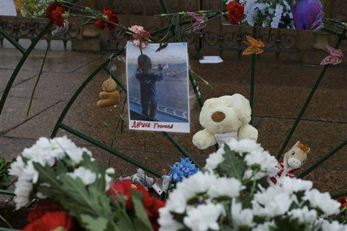 A portrait of 10 month Darina Gromova, a victim of a plane crash, is surrounded by flowers and toys attached to a fence at Dvortsovaya (Palace) Square in St.Petersburg, Russia, Wednesday.