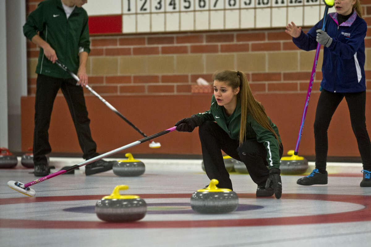 ERIN KIRKLAND   ekirkland@mdn.net Midland Curling Club member of the Willertz team Delaney Strouse, center, acts as skip and plans the next throw in the first seed's second game of the Great Lakes Curling Association Junior Championships on Tuesday at the Midland Curling Center. The tournament continues until tomorrow night. Winners of the GLCA Junior Championships will advance to the USCA National Junior Championships in Minn. from January 16-23.