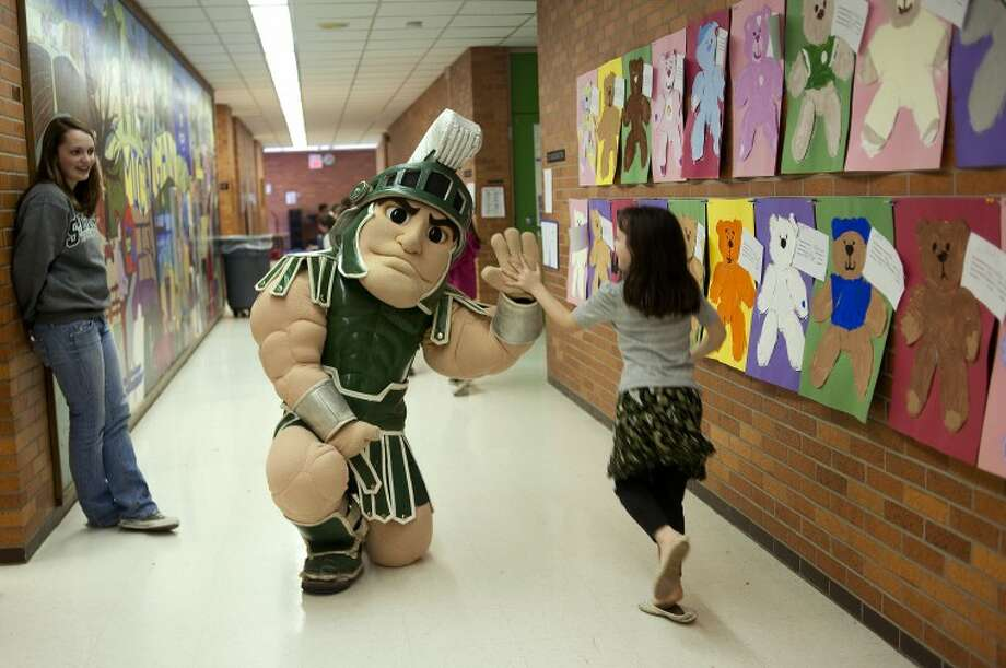 "NEIL BLAKE | nblake@mdn.netSparty, the mascot at Michigan State University, high fives a student at Woodcrest Elementary on Tuesday as MSU sophomore Erin Lucian looks on. Sparty made the rounds to Chestnut Hill, Plymouth and Woodcrest elementary schools promoting reading and leading students in cheers of ""Go green, go white!"" Photo: Neil Blake/Midland  Daily News"