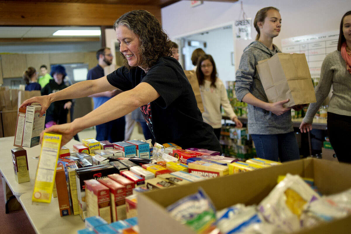 Elaine Tobey sorts food items to be packed up and bagged as Thanksgiving meals at Aldersgate United Methodist Church.