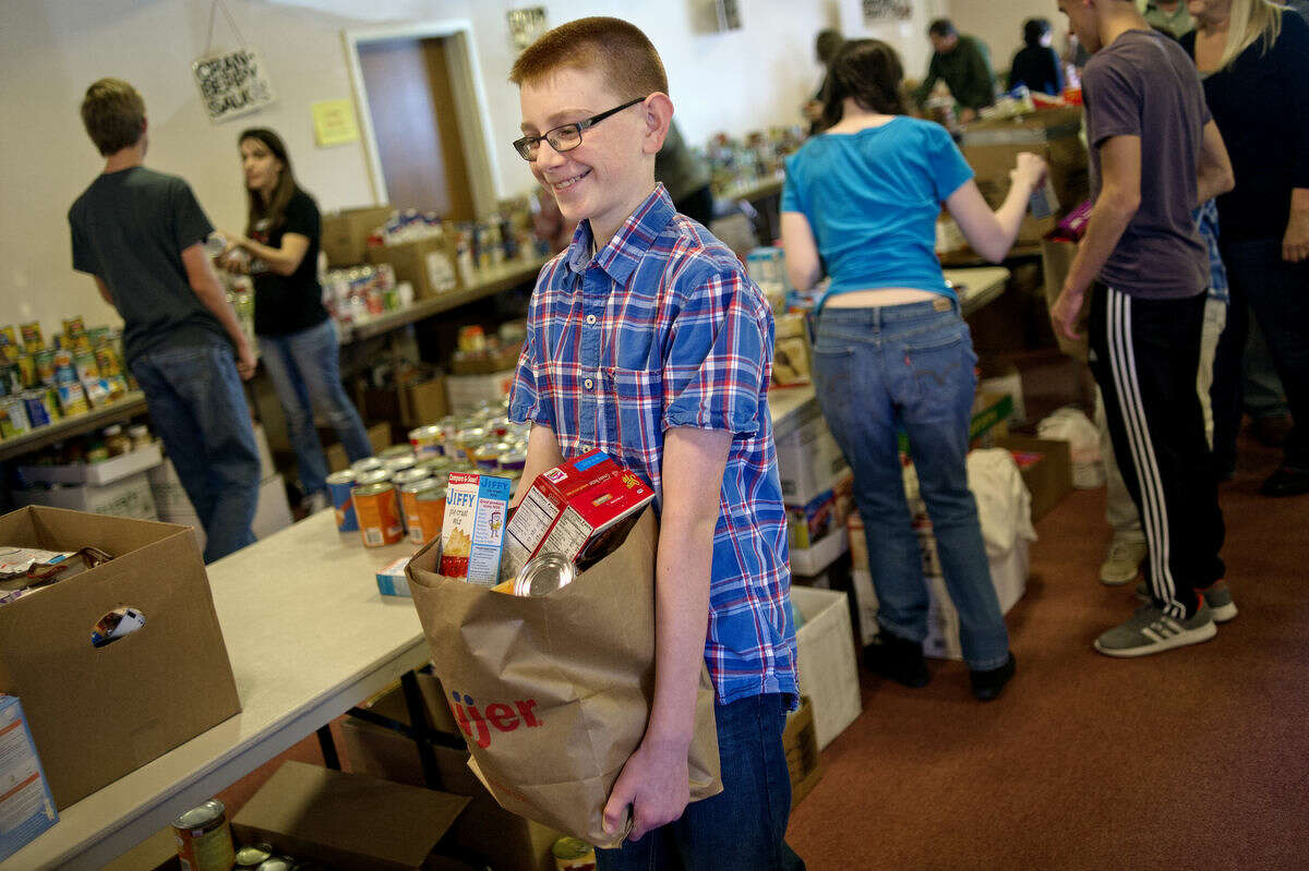 T.J. Smith, 12, packs up a bag containing a Thanksgiving meal at Aldersgate United Methodist Church.