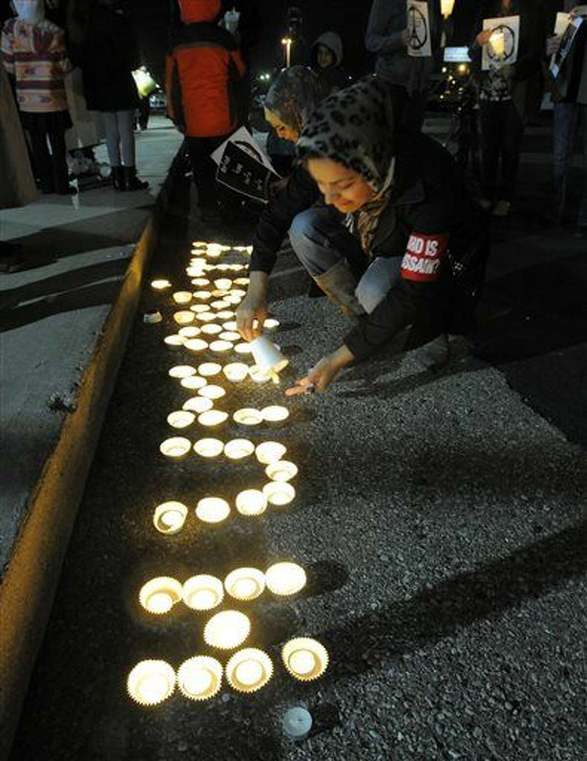 Sara Syeda, of Dearborn Heights, lights a candle in a group of candles spelling the word humanity on, Saturday during a candlelight vigil in support of the victims of the deadly Paris attacks and Beirut bombings at the Islamic Center of America in Dearborn.
