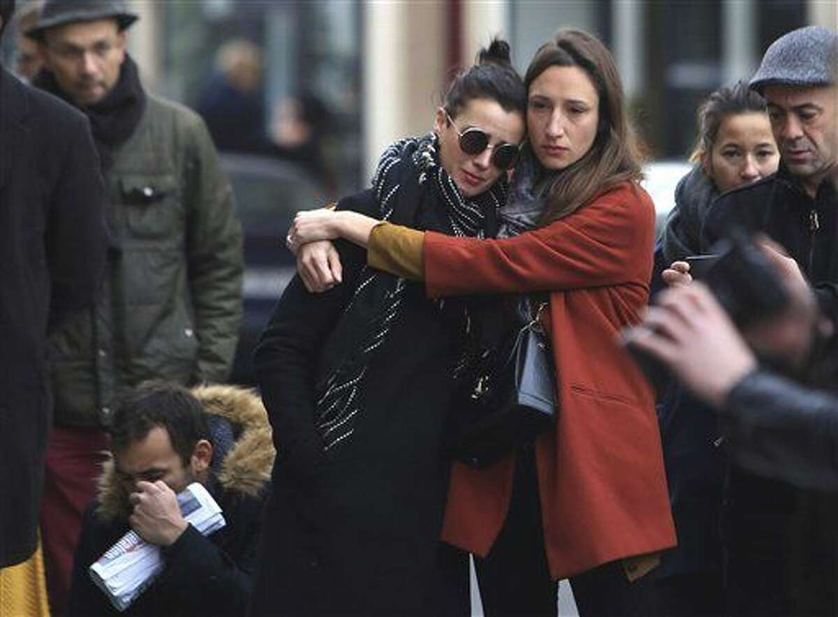 Women comfort each other as they stand in front of the Carillon cafe, in Paris, Saturday. French President Francois Hollande vowed to attack Islamic State without mercy as the jihadist group admitted responsibility Saturday for orchestrating the deadliest attacks inflicted on France since World War II.