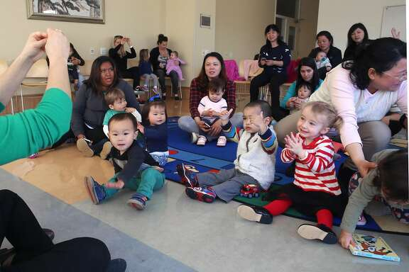 Children's librarian Andrea Yeager (left) leads Baby Rhyme time at the Mission Bay library in San Francisco, California,  on thursday, march 17, 2016.  At right Olivia Barkovik (red and white striped shirt), 21 months, claps her hands.