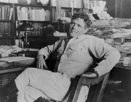 American author Jack London (1876-1916) reclines next to his desk in a wooden chair, smiling, his legs crossed. (Photo by Hulton Archive/Getty Images)