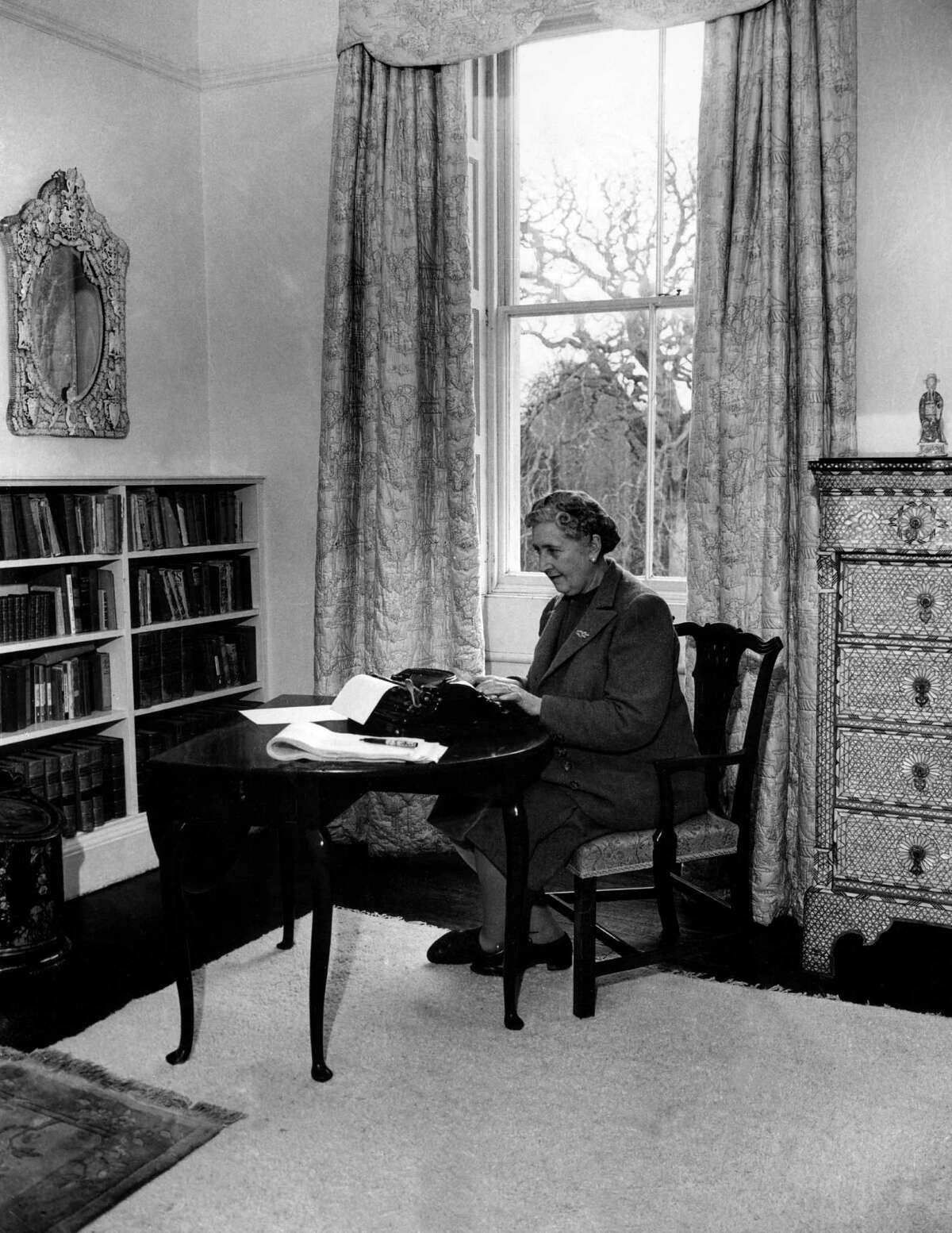 Dame Agatha Christie at work on her typewriter in her home, Greenway House, in Devonshire. Christie was famous for also working in her bathtub while eating lots of apples.