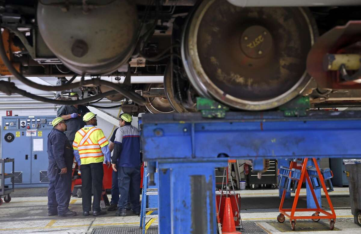 Workers inspect a train at the BART maintenance facility in Concord, Calif., on Thursday, March 17, 2016.