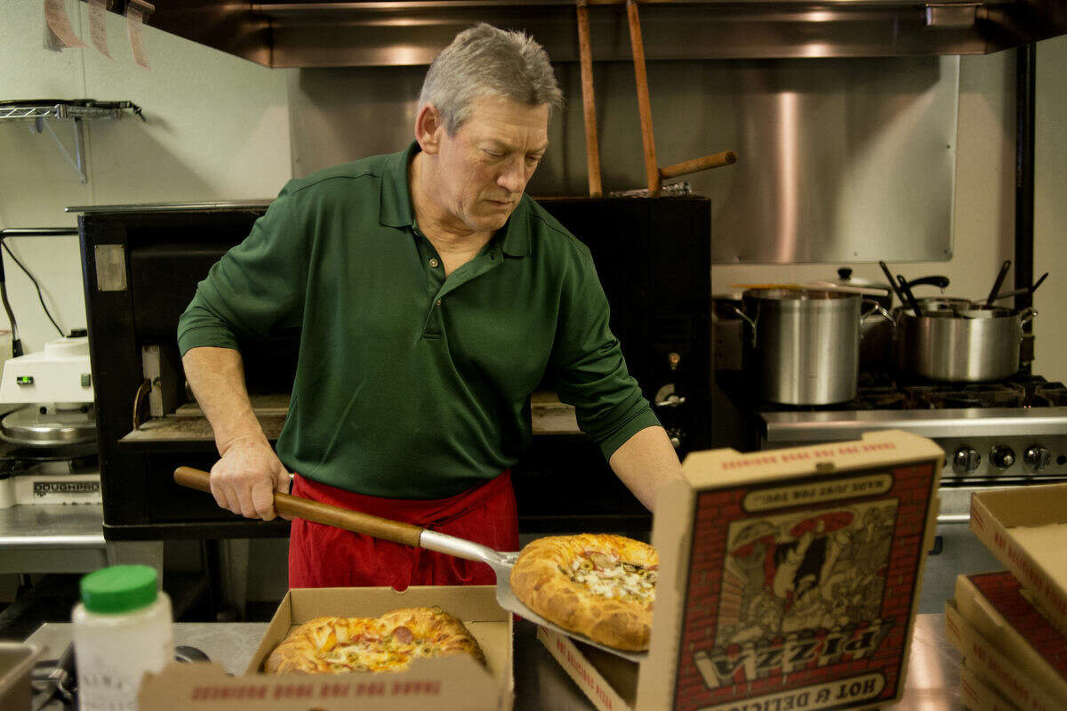 Paul Buffa, owner of The Brick Oven, pulls a pizza out of the oven during the lunchtime rush. Buffa recently opened the restaurant where he makes all the pizzas in the brick oven with his grandfather's pizza sauce.