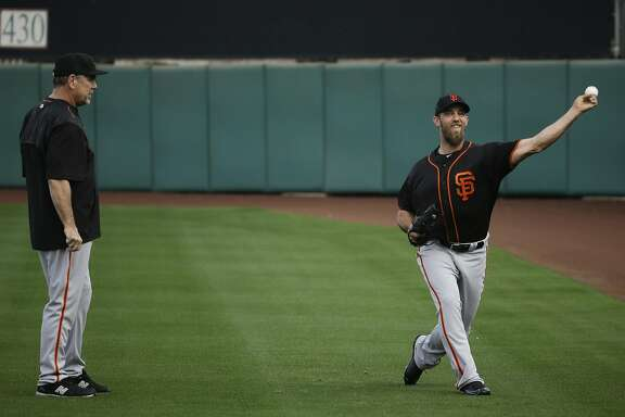 San Francisco Giants manager Bruce Bochy watches starting pitcher Madison Bumgarner throw during practice before the spring baseball season in Scottsdale, Ariz., Thursday, Feb. 18, 2016. (AP Photo/Chris Carlson)