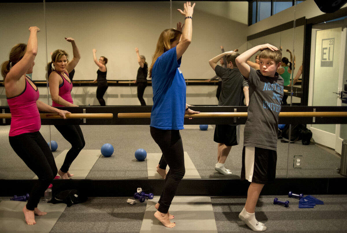 From left, Kim Rapanos of Midland and Carol Miller of Midland balance on their toes while 9-year-old Reese Hancock of Midland checks to see if he's performing the correct exercise as his mother Jennifer Gracey teaches a Barre22 class at Element22 in Midland.