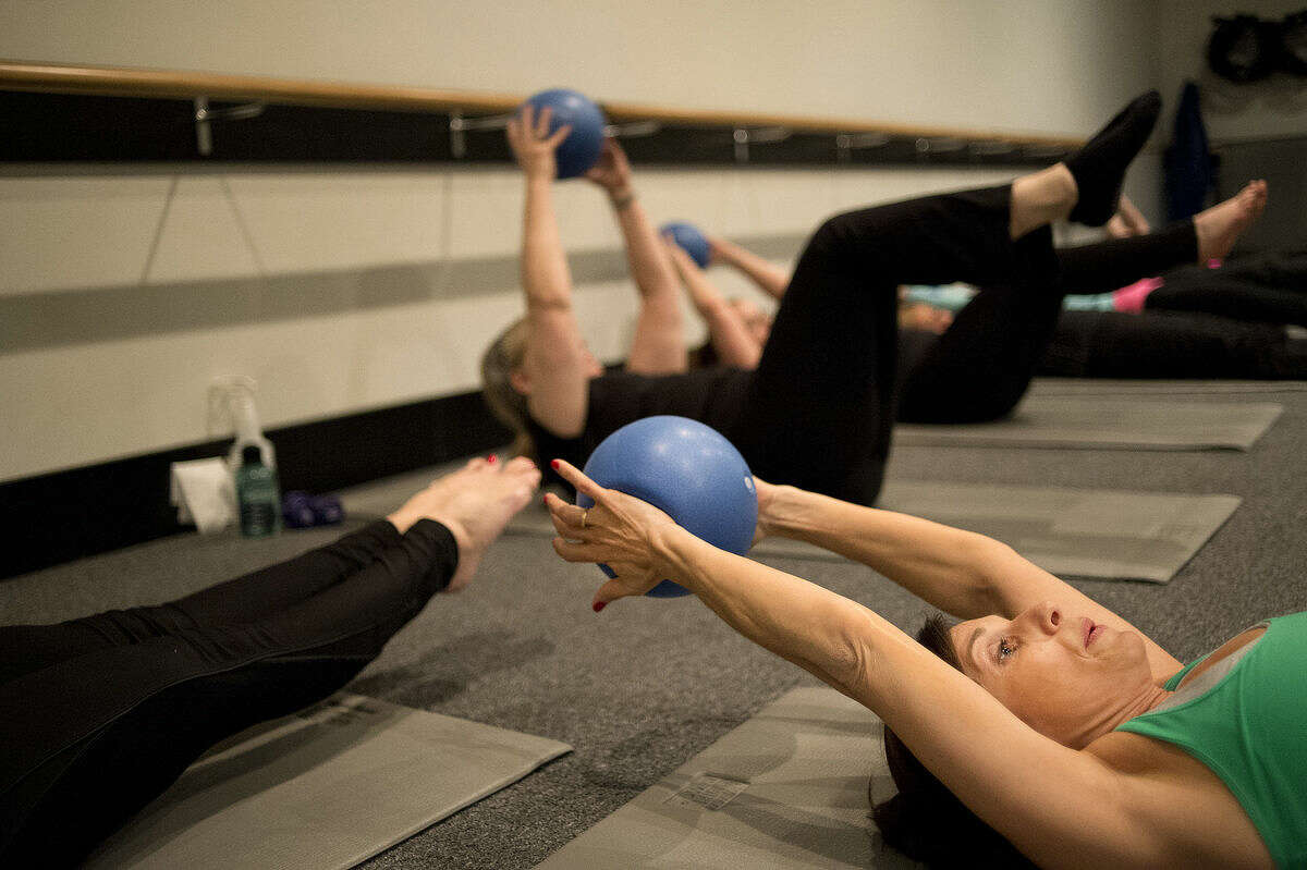 Lynn Tolfa of Midland stretches back during an abdominal exercise at Element22 in Midland.