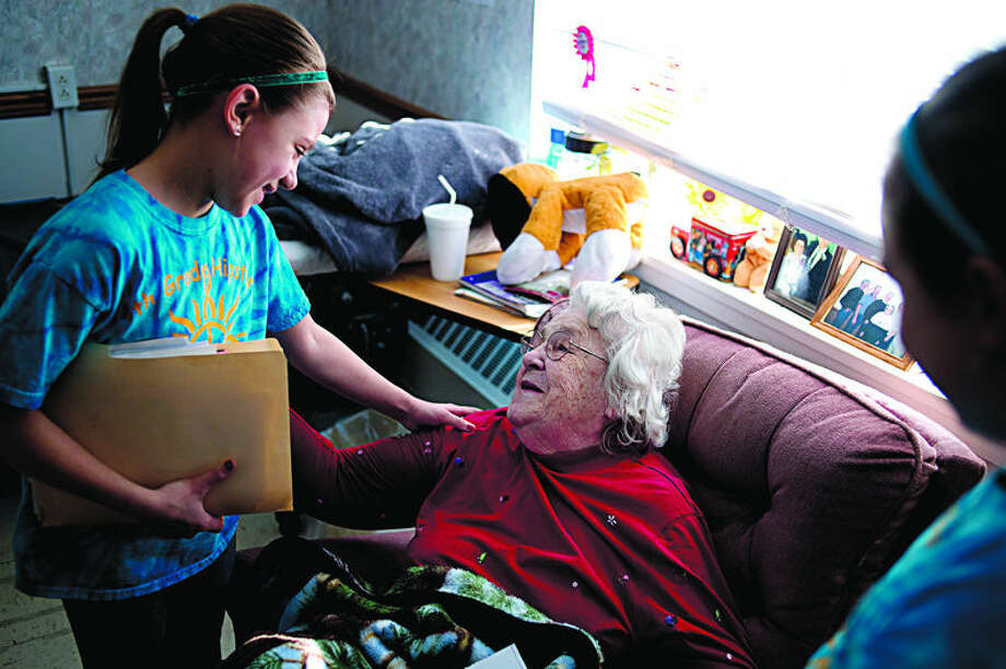 "Nine-year-old Emma Dodick, left, wishes Brittany Manor resident Anna Steinka a happy Valentine's Day with friend Natalie Nussear, 10, Saturday afternoon. Dodick got the idea for her fourth grade class at Blessed Sacrament to make Valentine's Day cards for the Brittany Manor residents after she spent time visiting her grandfather, Terry Berle, while he was in rehabilitation there. ""When she first came to visit she was a little scared,"" Berle said. ""By the second visit she warmed right up. It doesn't take her long to make a friend."" Photo: Brittney Lohmiller/Midland Daily"