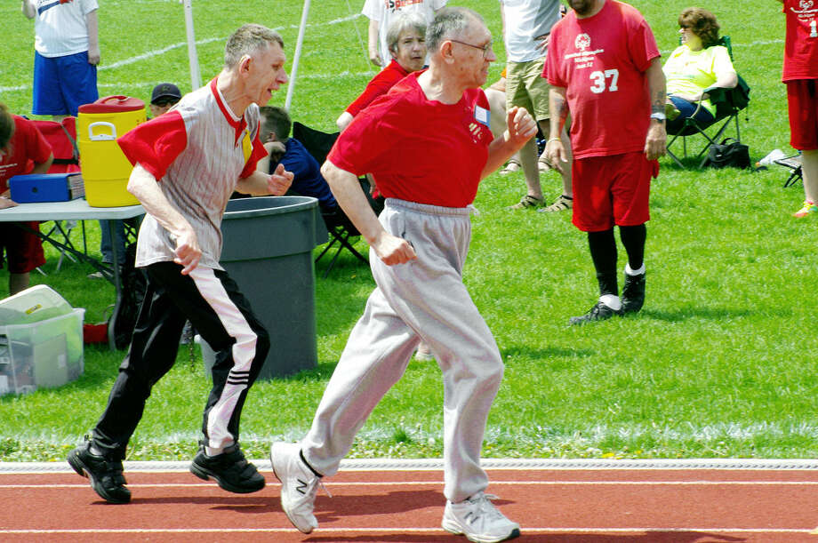 Brothers Jim (left) and Ricky Warner compete in a 50-meter dash heat Saturday during the annual Special Olympics track, field and bocce meet hosted by Midland County Special Olympics at the H.H. Dow High School track. Both received first place blue ribbons at the meet. Jim won the 50-meter dash heat and placed his hand on his brother's shoulder during that heat's ribbon award ceremony. Photo: Photos Provided
