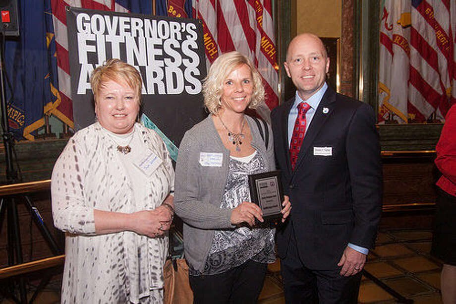Sue Lennon, director of employee health for MidMichigan Health, and Tina Parsons, wellness manager of MidMichigan Health, accept the award from James J. Tighe, CEO and president of Michigan Fitness Foundation. Photo: Photo Provided