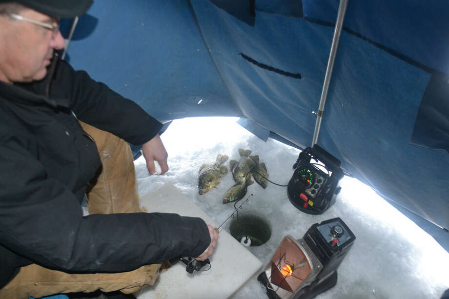 When an ice angler is prepared — as was Rick Craig of Midland in a portable shelter, foam beneath his feet, and a radiant propane heater going — he or she can focus on the fish-finding sonar and the fish, such as the crappies on the ice. Photo: STEVE GRIFFIN | For The Daily News