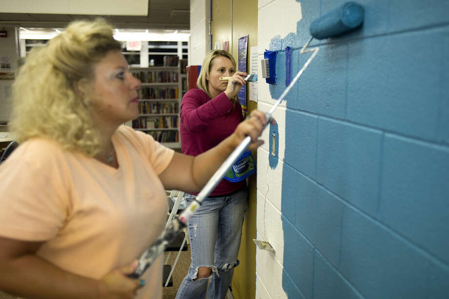 Kristi Kaye of Midland, left, and Natalie Smith of Beaverton, paint the library walls at Windover High School Tuesday afternoon. Photo: Brittney Lohmiller | Blohmiller@mdn.net